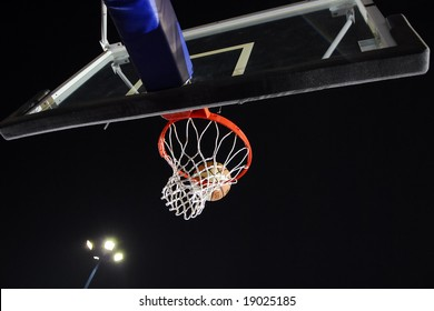 Ball coming to the hoop in a basketball arena
