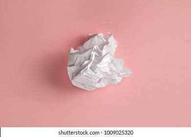 The the ball of crumpled white paper on a pink background. Minimalism concept.