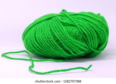 a ball of green wool in white background.