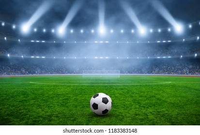 Ball on gras in soccer stadium with illumination at night