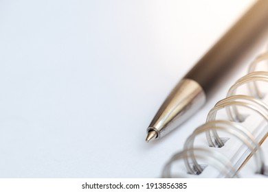 A ball pen on a white page of a notebook for investment planning