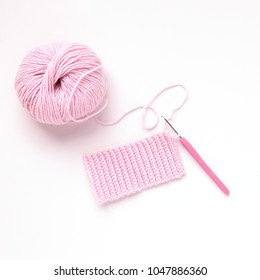 Ball of pink knitting yarn and knitting crochet on white background. Flat lay, top view. Handmade.