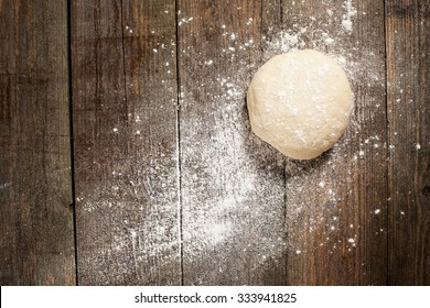 Ball of pizza dough on a rustic wooden background with dusting of flour