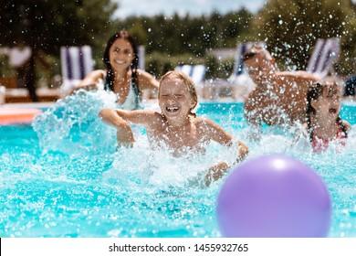 Ball im Pool. Fröhliche glückliche Eltern und Kinder, die beim Ball im Schwimmbad lachen
