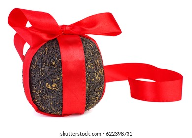 Ball of pressed big leaf black chinese tea tied with red ribbon isolated on white background