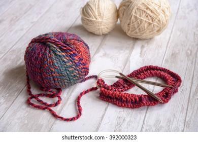 ball of purple and white yarn and knitting needles