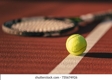 Ball and racket are lying on brown tennis court.