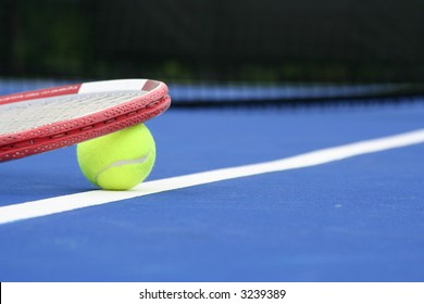 Ball and racquet on a blue court