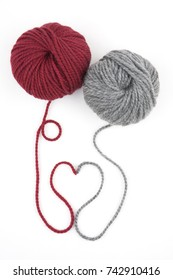 ball of red and grey yarn with heart on white background