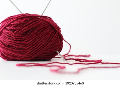 ball of red wool yarn and knitting needles