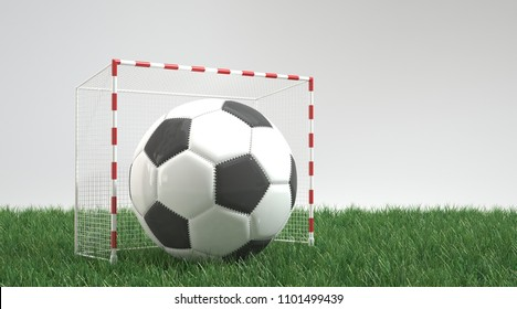 Ball in small football goal on green lawn against grey background with copy space. 3d Rendering