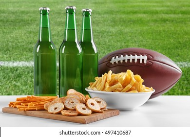 Ball, snacks and bottles of beer on green field background