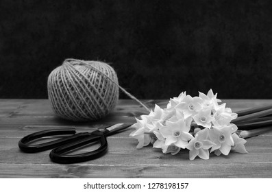 Ball of twine with retro flower scissors and white narcissi blooms on a wooden table - monochrome processing