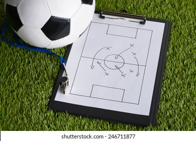 Ball; Whistle And Soccer Tactic Diagram On Paper Over Pitch