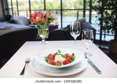 a ball of white ice cream with strawberries and mint on a white plate