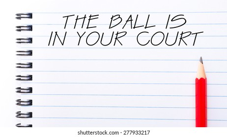 The Ball Is In Your  Court Text written on notebook page, red pencil on the right. Motivational Concept image