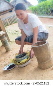 Ballapeu, Sulawesi, Indonesia - August 18, 2014: Unidentified young woman sifting coffee beans in the traditional way of Toraja, Sulawesi, Indonesia. Concept of manual working in developing countries.