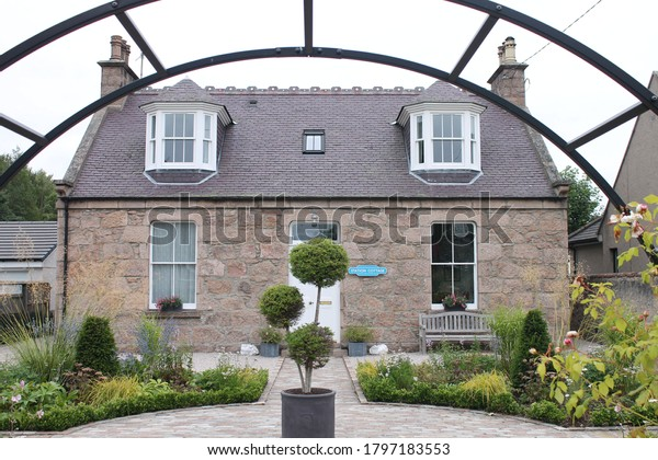 Ballater, Scotland, UK, 17/08/2020: Station cottage looking through a garden arch