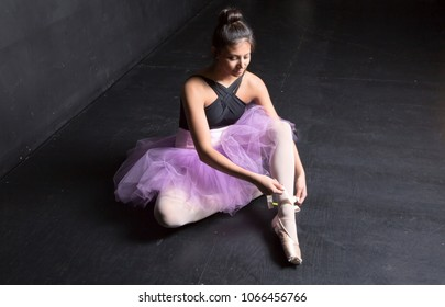 ballerina backstage tying pointe shoes