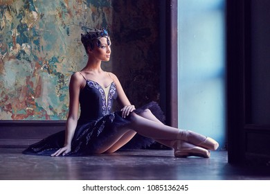 A ballerina in a beautiful suit by the window.