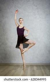 Ballerina in black dress in the studio grey background
