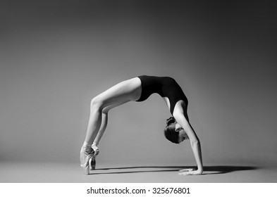 Ballerina in black outfit posing in bridge position. Studio background, grayscale image.