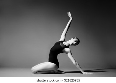 Ballerina in black outfit posing on studio background. Extreme flexibility, grayscale image.