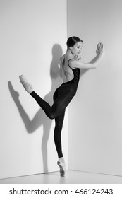 Ballerina in black outfit posing on pointe shoes, studio background.