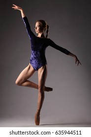 Ballerina in blue outfit posing on toes, studio background.