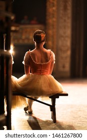 Ballerina in costume and pointe sits behind the scenes in the interval of performance