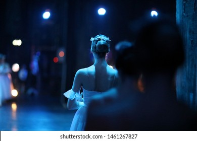 Ballerina in costume and pointe is standing backstage, waiting for the stage