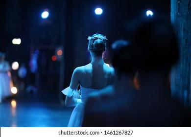Ballerina in Kostüm und Pointe steht im Hintergrund und wartet auf die Bühne