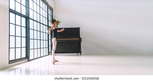 Ballerina cute little girl wear black ballet enjoy dancing with old piano in studio. Lovely kid girl pose dance ballet at indoor with reflections on the tiles floor.