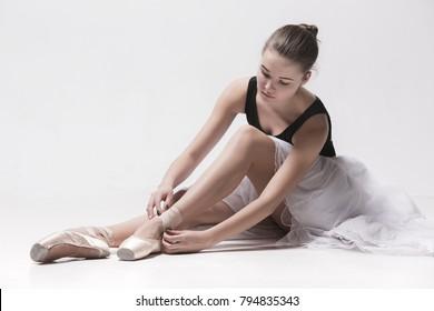 Ballerina dancer sitting down with her legs crossed