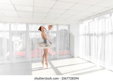 Ballerina dancer standing on tiptoe and holding on hands her little daughter