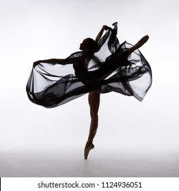 A ballerina dances with a black cloth. Color photo.