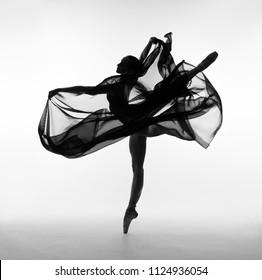 A ballerina dances with a black cloth. Black and white photo.