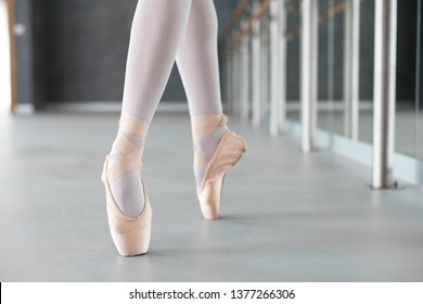 Ballerina is dancing in ballet pointe shoes. Close up of legs. Girl has workout in ballet class room.