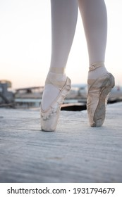 Ballerina dancing, closeup on legs and old shoes, standing in pointe position.