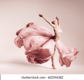 ballerina dancing in flowing pink dress in studio