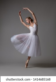 Ballerina dancing in white dress. Color photo.