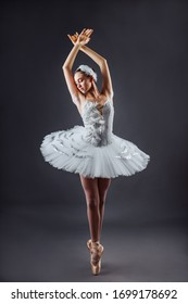 Ballerina dancing in white dress. Color photo. Graceful ballet dancer or classic ballerina dancing isolated on grey studio background. Ballerina on point shoes feet tutu from Lake Swan