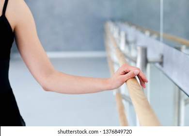 Ballerina is doing exercises in ballet modern school. Dancer is putting hand on barre by mirror. Girl has dance workout. Close up.