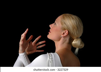 Ballerina expressing dramatism with her hands on black background
