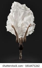 Ballerina Graceful Jump in White Silk Dress, Ballet Dancer Pointe Shoes in Fluttering Cloth, Black Background