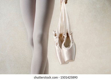 Ballerina is holding point shoes. Legs closeup