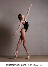 Ballerina in pointe shoes dancing in black clothes