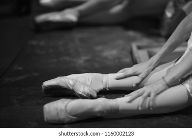 Ballerina in pointe shoes, sitting on the floor behind the scenes in the intermission of the ballet