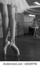 Ballerina in pointe shoes and tutu standing on toes at the bench. Reflection in the mirror in the ballet class. Classical ballet. Prima ballerina. Shooting close-up. Black and white photography
