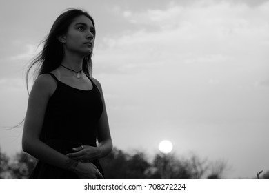 ballerina, portrait of beautiful woman with long dark hair over autumn field at sunset, thinking, hope, sadness, memory, loneliness, ballet motives, smoky eyes, deep intense look, monochrome